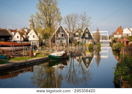 Edam, Netherlands - April 7, 2019: View Of Wooden Houses, Shipyard And Boats Along A Canal In The Hi