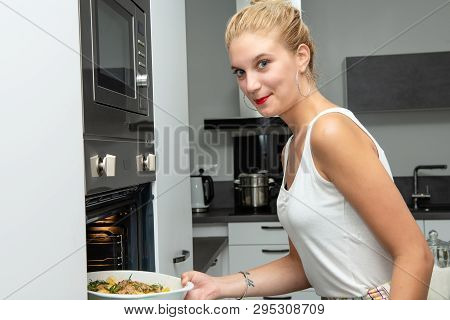 A Smiling Young Blond Woman Preparing The Meal In The Kitchen