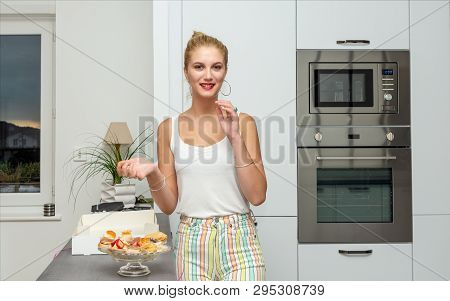 A Beautiful Young Blond Woman Eating Cakes In The Kitchen