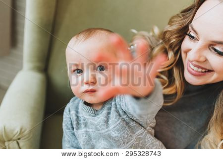 Beautiful Young Mother Holding Her Cute Son In Her Arms. Family, Togetherness.