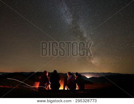Back View Group Of Four Young Friends Hikers Resting Together Around Bonfire Near Camp And Tourist T