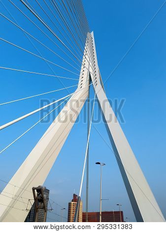 The Erasmus Bridge In The Rotterdam. White Metal Reliances On The Blue Sky Background With Sunlight.