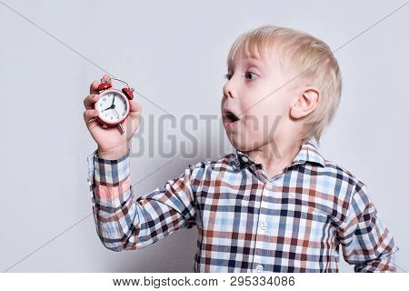 Little Blond Boy With A Red Alarm Clock In His Hands. Surprised Face. Morning Concept. Light Backgro
