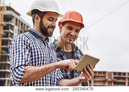 Working In Team. Two Young And Cheerful Builders In Protective Helmets Are Using Digital Tablet And