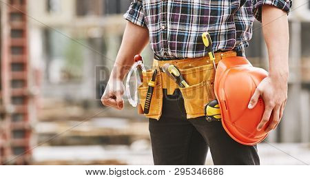 Safe Work. Cropped Photo Of Male Professional Builder With Construction Tools Holding A Safety Red H
