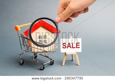 Magnifying Glass Is Looking At The Supermarket Cart With Houses And A Sale Poster. The Concept Of Se