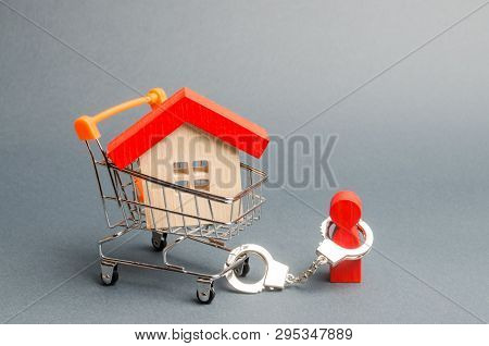 A Person Is Handcuffed To A House On A Supermarket Cart. The Concept Of A Large Debt On A Loan Or Mo
