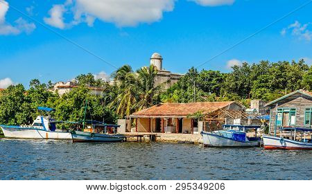 Cuban Fishing Boats And Village Houses With Jagua Spanish Castle Walls In The Background, Cienfuegos