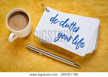 de-clutter your life  - handwriting on a stack of index cards with a cup of coffee and  a pen against yellow textured paper poster