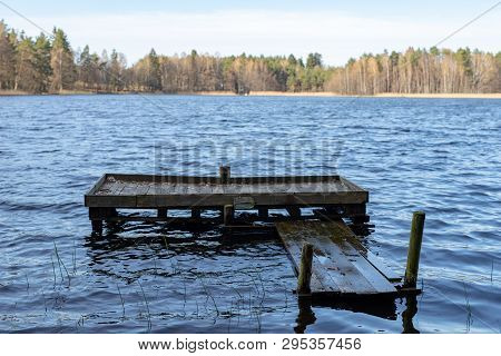 A Wooden Fishing Bridge Over A Small Lake. A Place To Catch Fish.