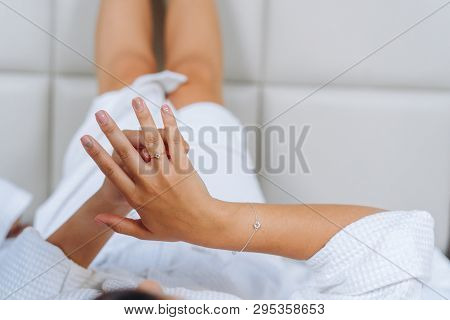 Male Hand Holds The Female Palm On Light Background.