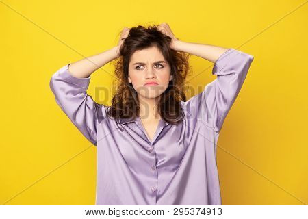 Annoyed young girl in pajamas grasping her hairs poster