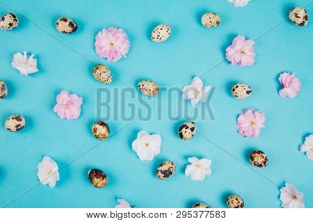 Quail Eggs And Pink Cherry Blossom Pattern On Blue Background, Flat Lay Style. Easter Concept.