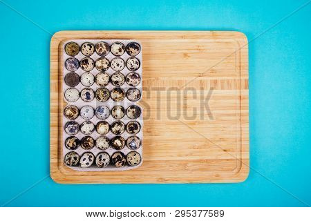 Quail Eggs In Paper Box On Wooden Board On Blue Background, Flat Lay Style.