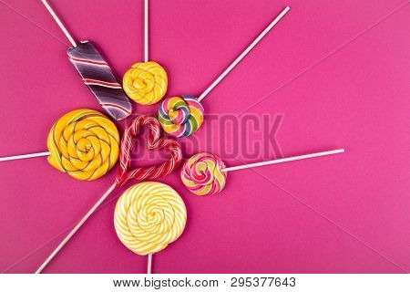 Many Colorful Lollipop Candys Arranged In Heap With Heart Shaped Candy In The Center On Pink Backgro