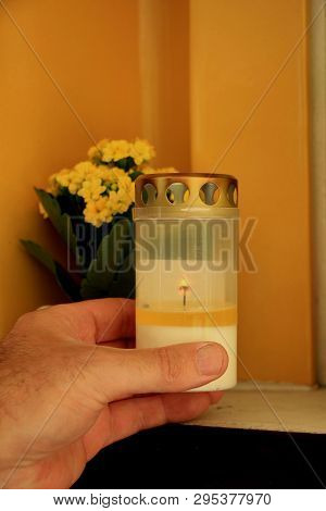 Man Lighting A Candle In A Columbarium Of A Crematorium