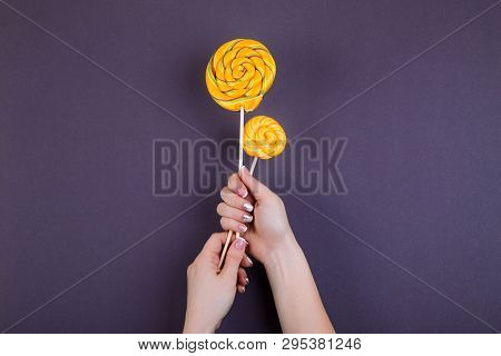 Concept Of Stylish French Manicure, Female Hand Holds Two  Coloroful Yellow Spiraled Round Lollypops