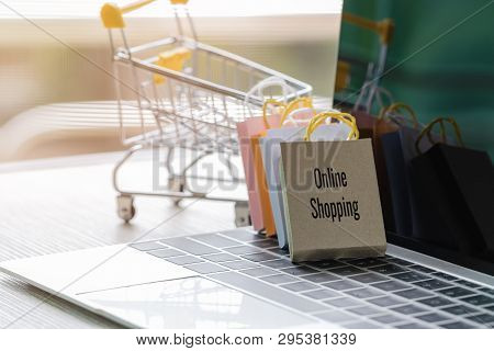 Colorful Paper Shopping Bags Leaning Trolley On Laptop Keyboard. Consumer Can Buy Products Directly