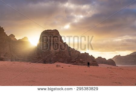 Landscape Of Wadi Rum Desert In Sunrise With A Man Walking Alone, And Sunlight Through Stone Mountai