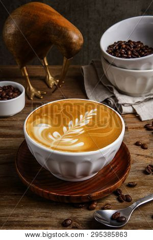 Latte Art In A Ceramic Cup With Coffee Beans