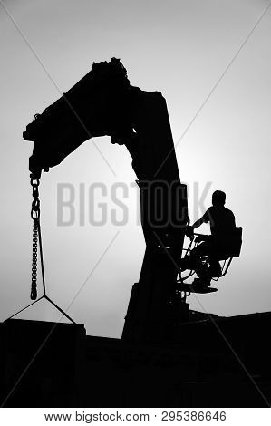 Silhouette Of Crane And Worker In Construction Site