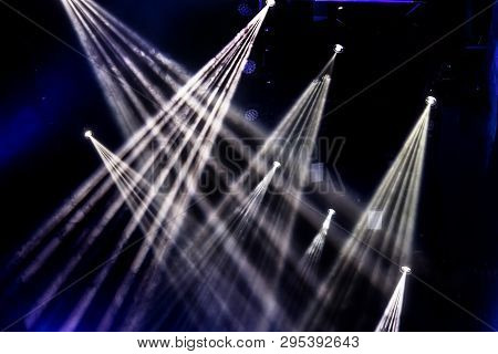 Stage Lights. Several Projectors In The Dark. Multi-colored Light Beams From The Stage Spotlights On