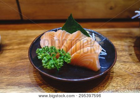 Japanese Food Sashimi Salmon In Black Plate Decoration With Vegetable On Wooden Table. Sashimi Is So
