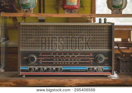 Vintage Retro Radio Transistor On The Wood Shelf. Old Media Sound And Music Equipment.