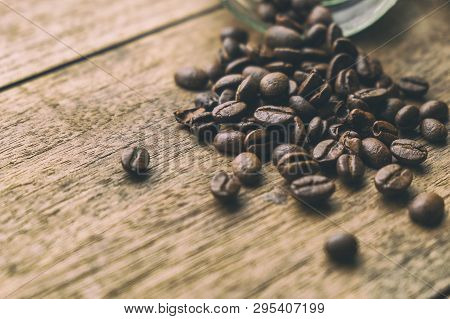 Coffee Beans On The Old Wood Table. Vintage Retro Style Picture Added.