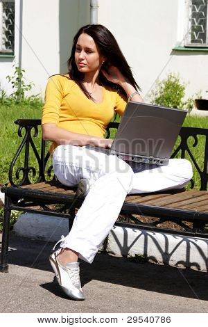 The young girl sits on a bench with laptop