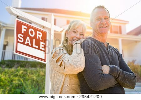 Attractive Middle-aged Couple In Front House and For Sale Real Estate Sign.