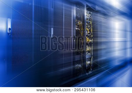 Server Racks Row In Big Data Center With Depth Of Field In Cool Blue Tone And Motion Effect