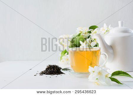 Cup of green jasmin tea white jasmine flowers, teapot. Teatime. Copy space. poster