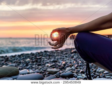 Silhouette Of Woman In Position Lotus, Practicing Yoga And Meditating On The Beach At Sunset