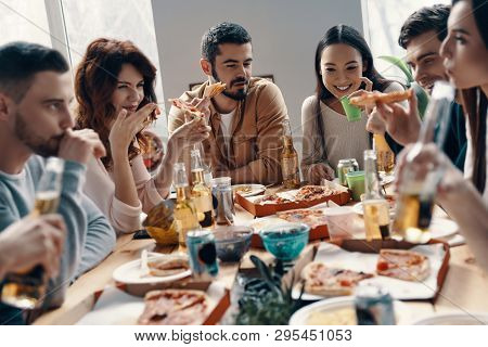 Happy To Be Around. Group Of Young People In Casual Wear Eating Pizza And Smiling While Having A Din
