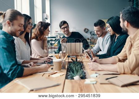 Marketing Team. Group Of Young Modern People In Smart Casual Wear Discussing Something While Working