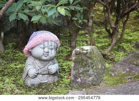 Stone statue of smiling Jizo (Jizo Bosatsu) in a knitted hat, Miyajima, Japan