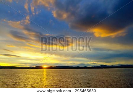Ocean sunset landscape - ocean waters lit by sunset summer light. Summer sunny water scene in colorful tones. Ocean summer nature with mountain range at the horizon