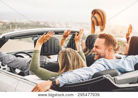 Group Of Friends Having Fun In Convertible Car During Road Trip At Sunset - Young Travel People Driv