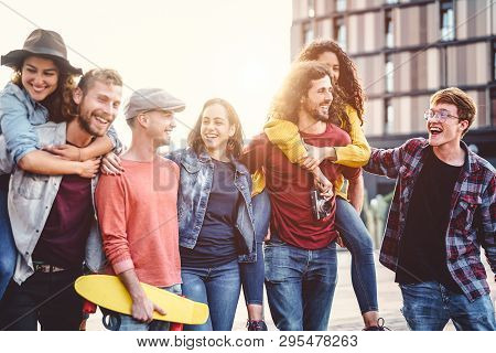 Group Of Young People Having Fun In The City Center - Happy Friends Piggybacking While Laughing And
