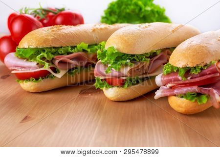 Three Sub Baguette Sandwiches  with Ham,  Turkey, Prosciutto, Cheese, Lettuce and Tomatoes on a wooden table closeup