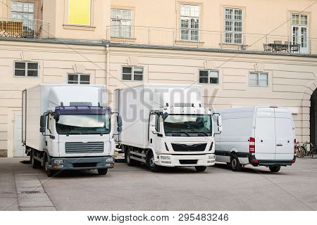 Different Small And Medium Courier Service  Trucks And Van At Building Courtyard. City Delivery Carg