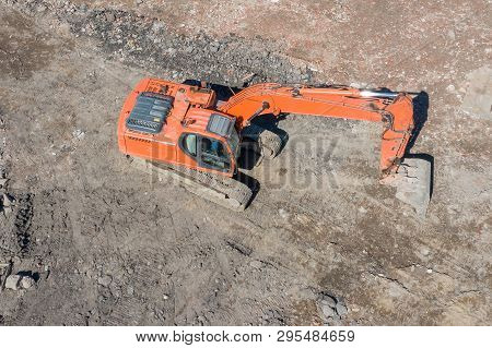 Orange Excavator On Caterpillars In The Foundation Pit During The Construction Of The Building Found