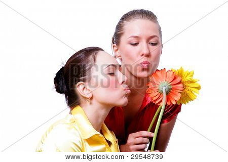 Two cheerful girls with flower  gerbers