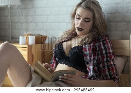 beautiful young blond woman in the bedroom on the bed in lingerie and shirt read book