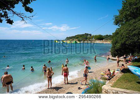 Porec, Croatia - July 17, 2018: Tourists And Holidaymakers On The Beach Of The Adriatic Sea Near Por