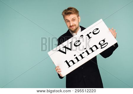 Happy Smiling Young Business Man Showing Signboard With Sign We Hiring, On Blue Background