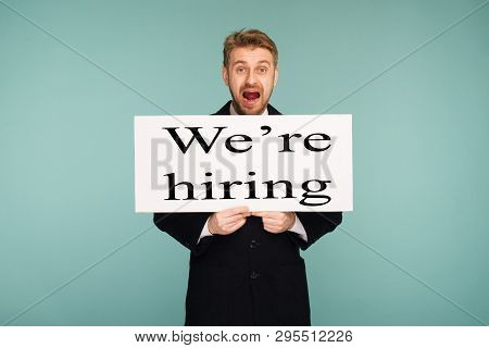 Spacey Mature Business Man Showing Signboard With Sign We Hiring, On Blue Background