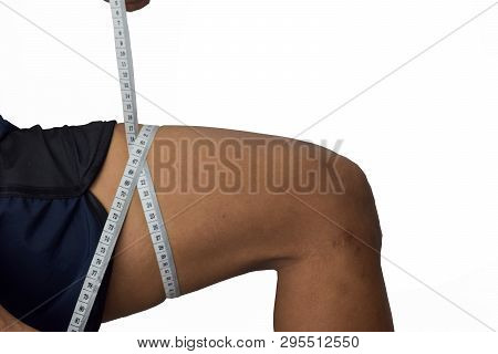 Athlete Measures Calves Of His Thigh. Checking His Thigh. Selective Focus In Pants. Isolated On Whit