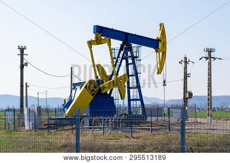 Blue And Yellow Pump Jack Above An Oil Well Surrounded By Electricity Poles And Protected With A Fen